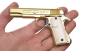 Colt М 1911 A1 Pistol, gold-plated miniature model in hand